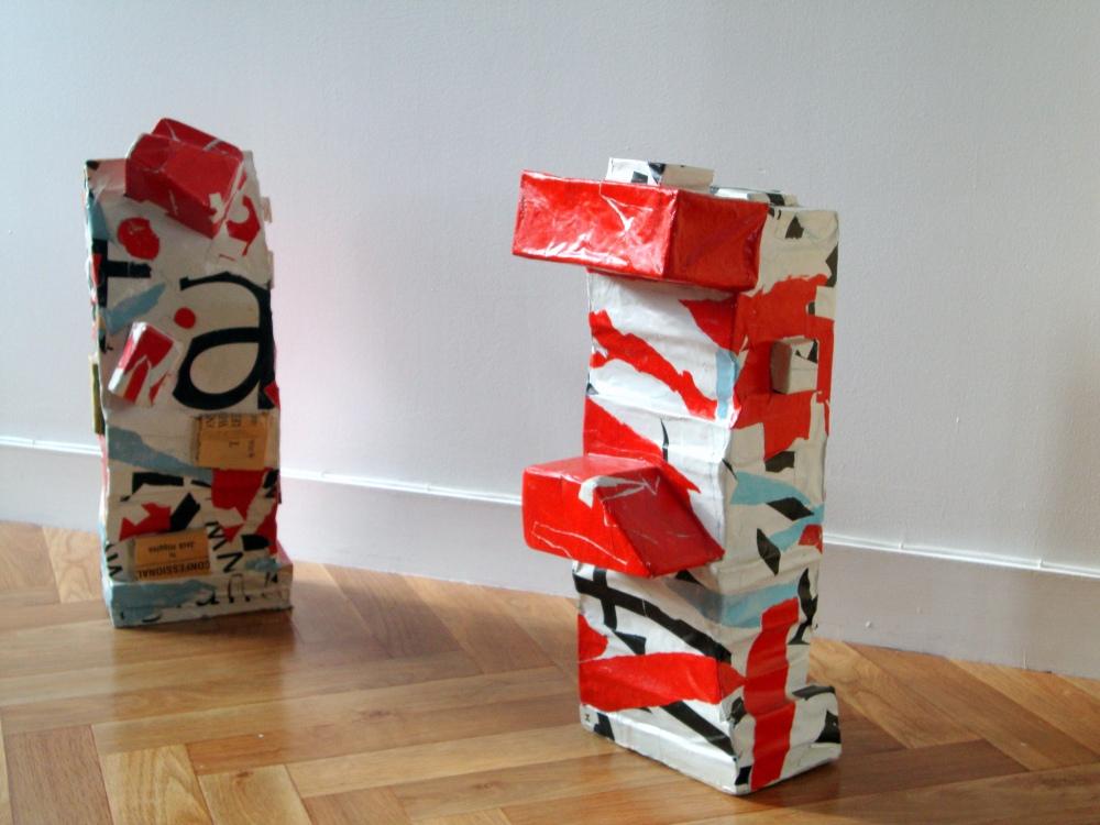 deux sculptures rouge et blanches composées de livres empilés et recouvert de papier d'affiche