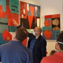 artiste peintre montrant sa toile lors d'un vernissage