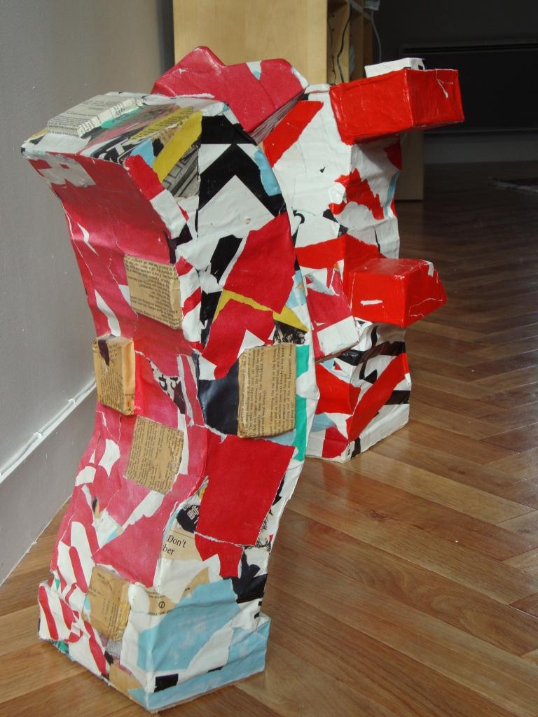 deux sculptures rouge et blanches composées de livres empilés et recouvert de papier d'affiche Ensemble de deux sculptures livres recyclage